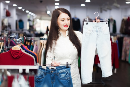 hellion: Woman choosing jeans at clothing store Stock Photo