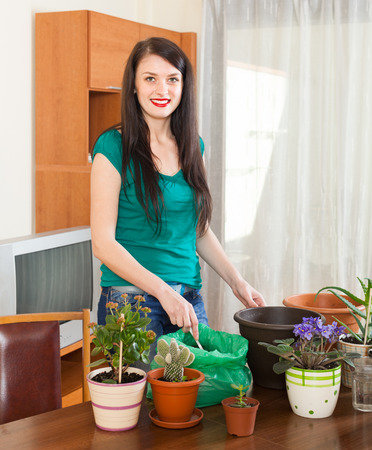 Female gardener with flowering plants in pots at home photo