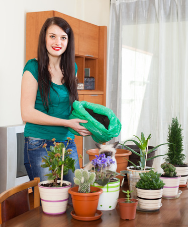 Happy girl transplanting flowers plant in flowerpot  photo