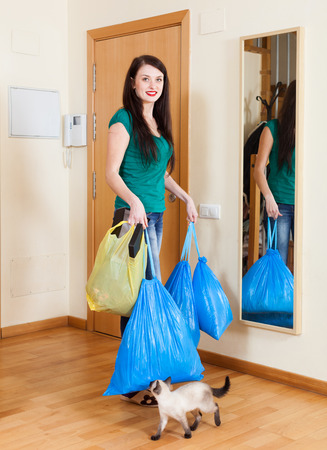 brunette woman near door with garbage  at home photo