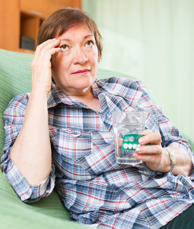 Tired senior woman sitting on sofa and holding glass of water and medicine photo