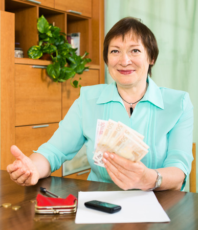 Happy mature woman with financial documents and money indoor photo