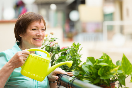 Smiling positive senior woman watering decorative flowers on balcony photo