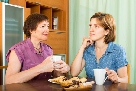 Elderly woman talking with her young daughter and during tea-drinking photo