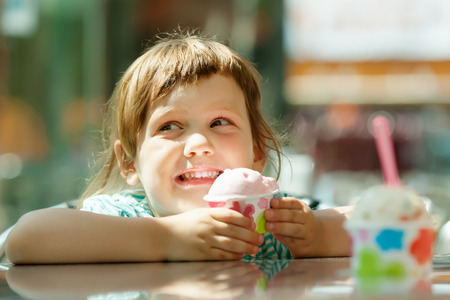 child eating ice cream in outdoor cafe  photo