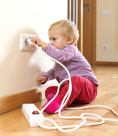 Adorable toddler playing with electricity at home in the floor photo