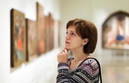 Vrouwelijke bezoeker uitziende foto's in kunstgalerie Stockfoto