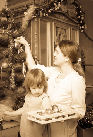 Retro photo of young woman  and child preparing for  Christmas at home photo