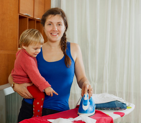 Happy  housewife with baby ironing with iron at home