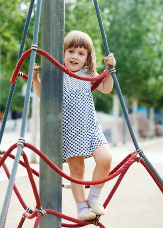 adroitness:  child climbing at ropes on playground area in summer