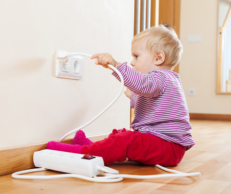Toddler playing with electricity on floor photo