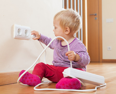 Toddler playing with extension cord at home photo
