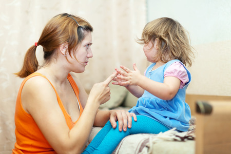 berate: Woman scolds crying child at home interior Stock Photo