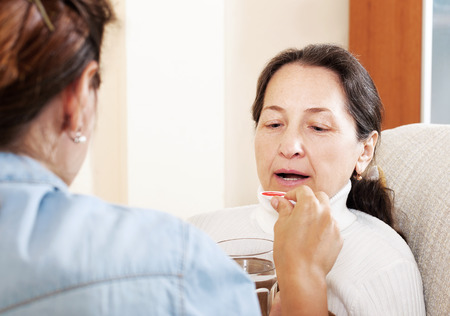 medicament: daughter giving medicament to mother at home Stock Photo