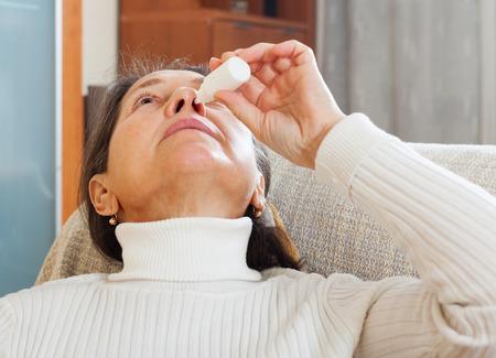 nosotrophy: Mature woman dripping nasal drops at home