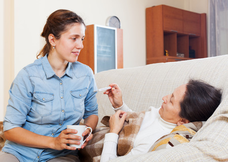 nosotrophy: Adult daughter caring for sick mother who has high temperature in living room Stock Photo