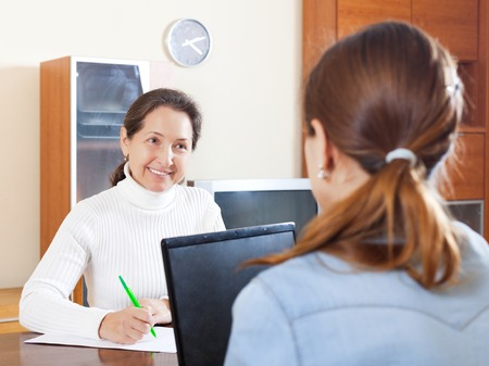 outreach: Mature woman answer questions of outreach worker with laptop at table in home Stock Photo