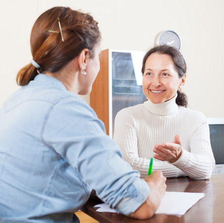 Happy senior woman answer questions of social worker in home Imagens - 28750219