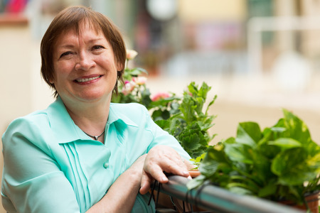 Cheerful senior woman sitting on balcony and smiling photo