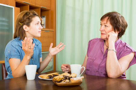 Female pensioner chatting with her daughter during tea-drinking photo