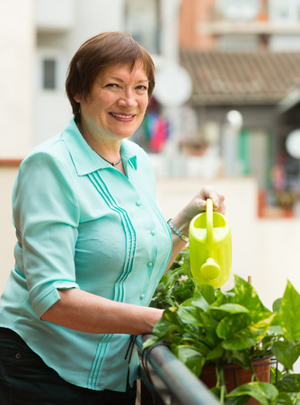 Smiling aged woman watering decorative flowers on balcony photo