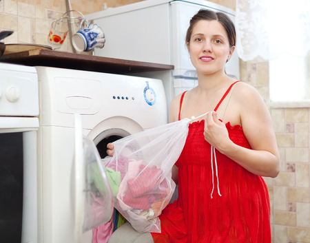 Smiling woman  in red  loading the washing machine with laundry bag in kitchen photo