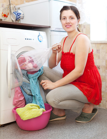 housewife  in red  loading the washing machine with laundry bag at home photo
