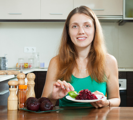 woman in green eating boiled beets at  kitchen