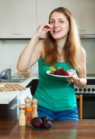 ordinary woman: Happy ordinary woman in green eating boiled beets at home