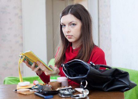 ransack: Young woman looking for something in her purse Stock Photo