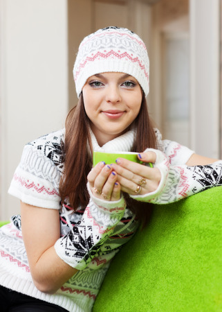 casualy: Young woman warms with cup of tea at house in winter Stock Photo