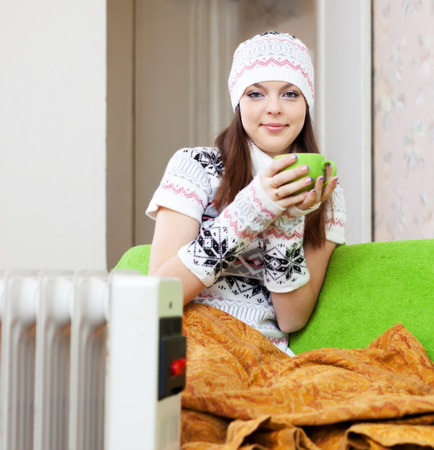 woman in hat with cup near warm radiator at home Stock Photo