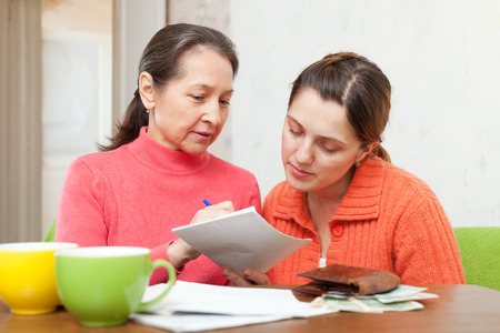 utility payments: Mature mother scolds adult daughter for utility payments bills or credits
