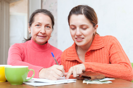 utility payments: Two positive women fills in utility payments bills at  home Stock Photo