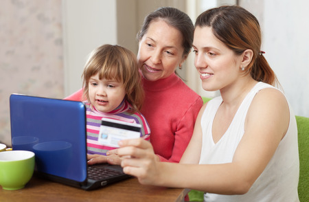 Happy family of three generations  shopping on internet from home, using laptop and paying with credit card photo