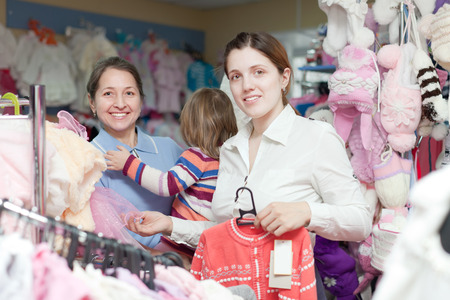 Two women and child  chooses wear at childrens clothes shop photo
