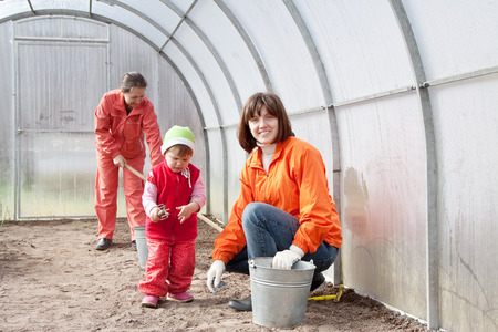 organics:  Happy women with child works at hothouse in spring Stock Photo