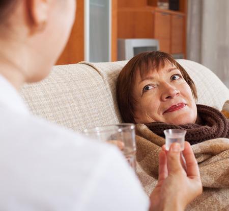 medicament: enfermera da el jarabe de medicamento para madurar mujer