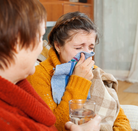 sick woman with running nose uses handkerchief in home Stock Photo