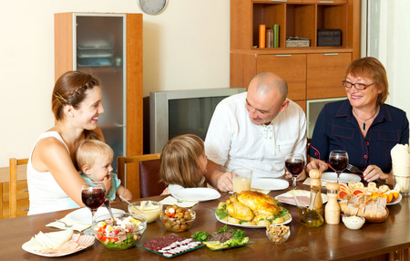 Happy three generations family eating chicken over  table at home interior Stock Photo