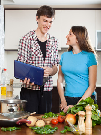 Happy young couple cooking with notebook in home kitchen photo