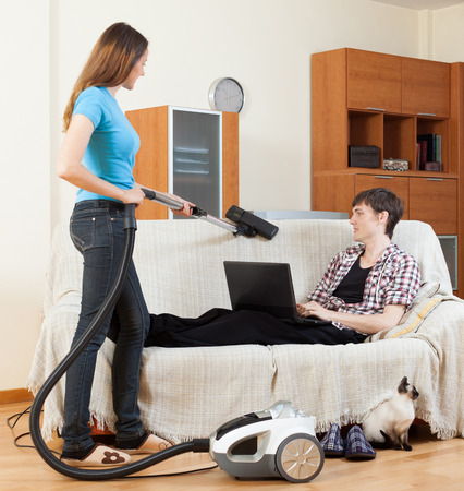 Girl cleaning with vaccuumcleaner while young man with notebook resting over sofa photo