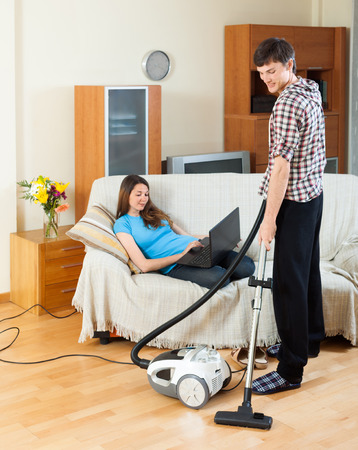 vaccuum: Man doing house cleaning with vaccuum cleaner while girl  with laptop  resting over sofa Stock Photo