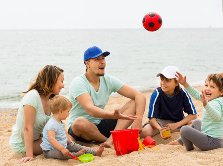 Happy family playing with ball at sandy beach  at summer day photo