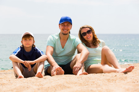 Happy smiling couple with son at sandy beach in summer day photo