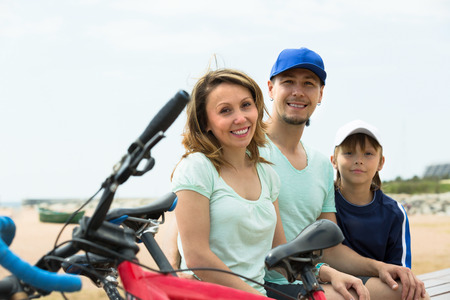 Positive parents and boy with bicycles at seashore photo