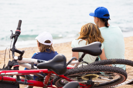 Smiling parents with kid having rest after cycling on the beach photo