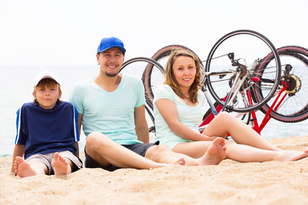 Happy parents with kid having rest after cycling on sandy beach photo