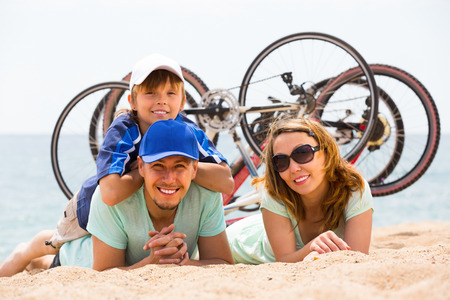 Couple with son lying on sand with bicycles at seashore  photo