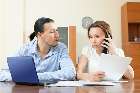 Adult couple calling by mobile about financial documents at home interior photo